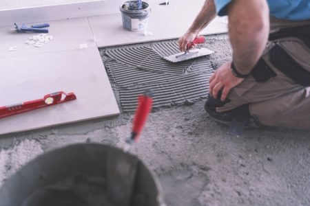 Cropped image of adult builder spreading and smoothing tile adhesive on the floor